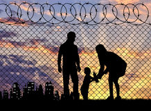 Silhouette of refugee families. Concept of the family of refugees. Silhouette of refugee families near the fence on the border on the background of the city in royalty free stock photo
