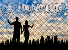 Silhouette of refugee families. Concept of the refugees. Silhouette of refugee families near the fence on the background of the city and sunset stock photos