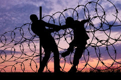 Silhouette of refugees and barbed wire Royalty Free Stock Photography