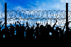 Silhouette of refugees and barbed wire. Concept of security. Silhouette of refugees climb over the barbed wire at the border Stock Photography