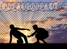 Silhouette of refugees crossed the border. Concept of the refugees. Silhouette of refugees crossed the border illegally through the hole in the fence Stock Images