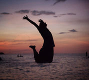 Silhouette of a relaxed man jumping on the beach Royalty Free Stock Photo