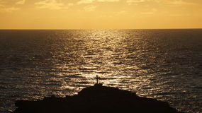 Silhouette of a religious Cross Crucifix against the sea. A silhouette shot of a Crucifix on the rocks at Malin Head in Ireland, taken against the sea glistening Stock Images