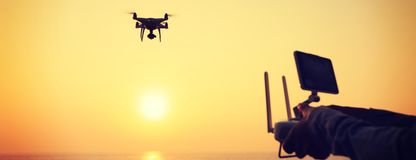remote control a flying drone which taking photo over sunrise sea Royalty Free Stock Images