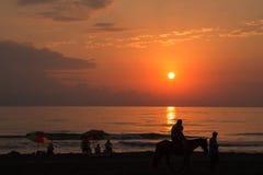 Silhouette renversante des personnes sur l'arénacé Un peuple sur la plage et mer dehors au coucher du soleil Photos stock