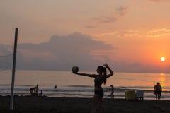 Silhouette renversante des personnes sur l'arénacé Un peuple sur la plage et mer dehors au coucher du soleil Image libre de droits