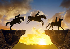 Silhouette of a rider on a horse jumping through the gap between rock Royalty Free Stock Image