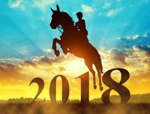 Silhouette the rider on the horse jumping into the New Year 2018. Silhouette the rider on the horse jumping into the New Year 2018 at sunset Stock Photos