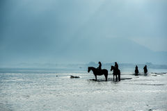 Silhouette of Riders at the beach riding horses Stock Photo