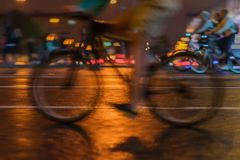 Silhouette of riding Cyclists on the city roadway, night light, bokeh, close-up of wheels and legs, abstract, motion Royalty Free Stock Photos