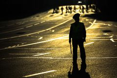 Silhouette of road policemen regulating traffic jam on the city center. Royalty Free Stock Images