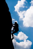 Silhouette of a rock climber. With rope ascending sheer face of mountain with blue sky and cloud background Stock Images