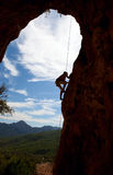 Silhouette of rock climber climbing the cliff Stock Images
