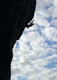 Silhouette of rock climber climbing cliff royalty free stock images