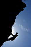 Silhouette of a rock climber hanging on the wall stock photography