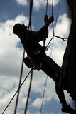 Silhouette of rock climber lowering down cliff stock images