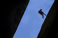 Silhouette of rock climber rappelling. A crack with blue sky behind Stock Images