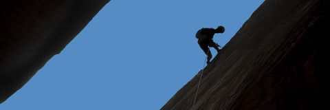 Silhouette of rock climber rappelling Stock Images