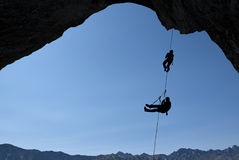 Silhouette of rock climbers over blue sky background Stock Image