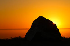 Silhouette of rock with sun Stock Images