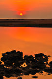 Silhouette rock and sunset at the beach Stock Image