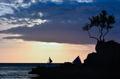 Silhouette of a rock and a tree. With some boats in background at sunset in Boracay, Philippines stock photo