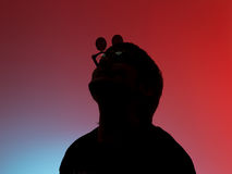Silhouette Rocker man in a funny glasses posing on red background Stock Photo