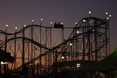 Silhouette of rollercoaster at sunset royalty free stock image