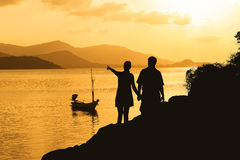 Silhouette of romance couple standing on a rock Royalty Free Stock Photos