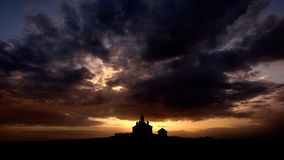 Silhouette of Romanian church with ray light after storm Stock Image
