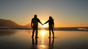 Silhouette of a romantic couple. Concept of love and happiness. Silhouette of a romantic couple holding hands on the beach at Cape Town city, South Africa. Man Stock Photo
