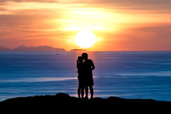 Silhouette of romantic a couple hug kissing against a sunset sky Royalty Free Stock Photo