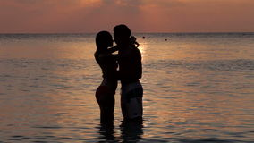 Silhouette Of Romantic Couple Kissing In Sea stock video