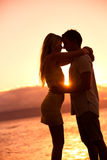 Silhouette of Romantic Couple Kissing at Sunset Stock Photography