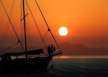 Silhouette romantic couple in love on sailboat Stock Image