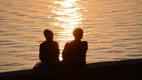 Silhouette of romantic couple in love at sunset at the sea. Boy and girl enjoying at sunset and taking selfie with phones on holid stock footage
