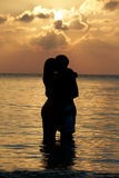 Silhouette Of Romantic Couple Standing In Sea Stock Photo