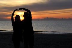 Silhouette of romantic honeymoon couple on the beach Stock Photos