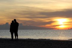 Silhouette of romantic honeymoon couple walking on the beach. With beautiful sunrise background Stock Photo