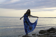 Silhouette of romantic woman standing on a rock by the sea dress. Like a sail, natural light and shadows Stock Image