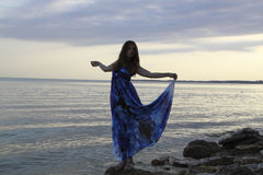 Silhouette of romantic woman standing on a rock by the sea dress. Like a sail, natural light and shadows Stock Photo