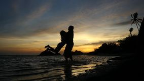 Silhouette of romantic young couple spinning around at amazing sunset, slow motion. 1920x1080. Hd stock footage