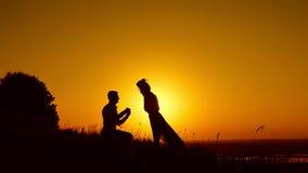 Silhouette romantique de l'homme obtenant vers le bas sur son genou et proposant à la femme sur le pré d'été - le couple se fianc banque de vidéos