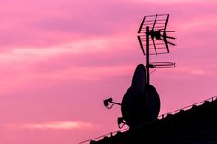 Silhouette of roof with satellite and antenna on nice vibrant vi Stock Image