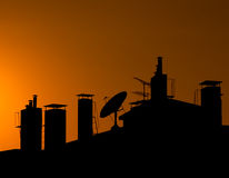 Silhouette of a Roof Top with Chimneys Stock Photo