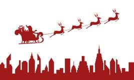 silhouette rouge Le père noël volant au-dessus d'une ville avec le traîneau de renne Photo stock