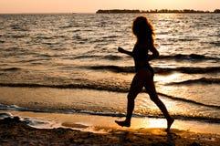 Silhouette rougeoyante foncée de femme fonctionnant le long de la plage image stock