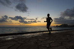 Silhouette of runner jogging along beach Stock Photography