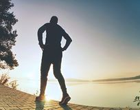 Silhouette of runner man along on the beach at sunset with sun royalty free stock images