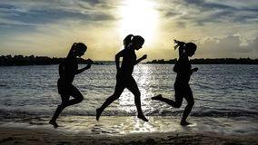 Silhouette of runner woman, running on the beach at sunset stock images